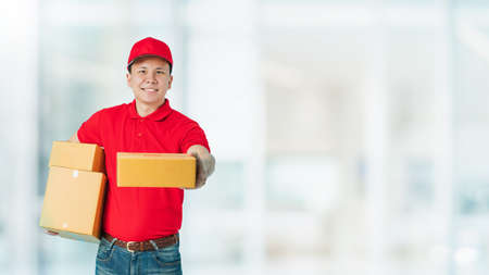 Asian happy delivery man wearing a red shirt carrying paper parcel boxes isolated on blur interior shopping mall banner background.Concept of Postal delivery service.