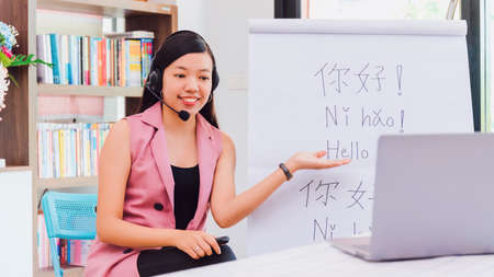 Asian woman teacher teaching remotely at home office with online technology laptop.Teaching Chinese language for Students at home school.Translation on paper text