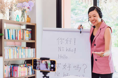 Asian woman teacher teaching remotely at home office with online technology smartphone.Teaching Chinese language for Students at home school.Translation on paper text
