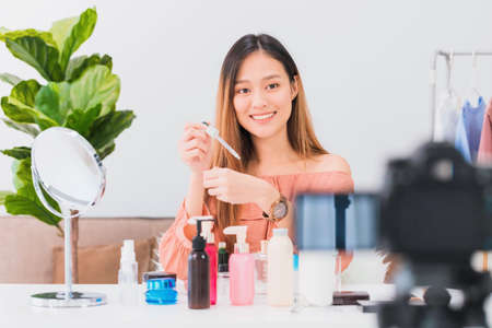 Beautiful asian woman blogger is showing how to make up and use cosmetics in front of the mirror and recording vlog video live streaming at home.Skincare for healthy face concept.