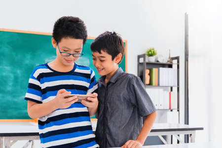 Asian happy school boy with friend learning and playing game with smartphone on black board background with smiling face.Creative education of kid student concept. Foto de archivo