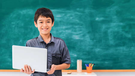 Asian happy school boy holding laptop on black board background with copy space.Creative education of kid student concept.