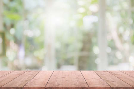 Empty wood table top and blurred of interior restaurant with window view green from tree garden background background - can used for display or montage your products. Foto de archivo