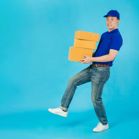 Asian happy delivery man carrying paper parcel boxes isolated on blue colour background.Concept of Postal delivery service.