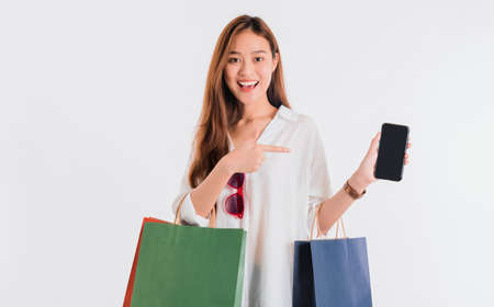 Asian beautiful women blogger are using the smartphone shopping online with a shopping bag in white color background with copy space.Concept of online shopping business with Promotion and Sale.