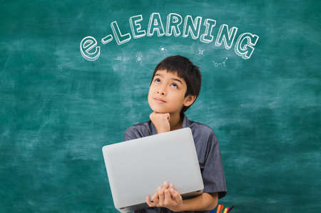 Asian happy school boy thinking and holding laptop on black board with e-learning text background.Creative online education of kid student concept.