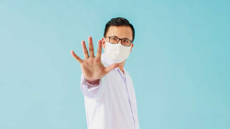 Portrait of Asian medical male Doctor wear a mask to prevent germs and standing and raising hand to show the symbol of stop isolated on blue background.Concept of preventing infectious diseases.