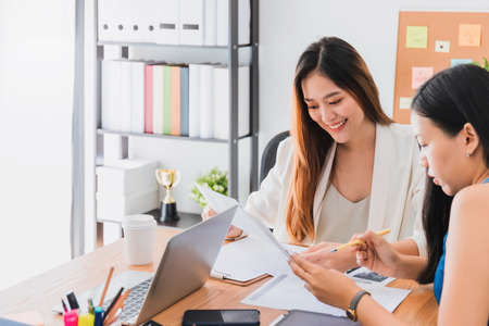 Asian beautiful empower woman smiling and talking with friend working at meeting room in office interior background with copy space.Owner businesswoman startup with confident and cheerful.