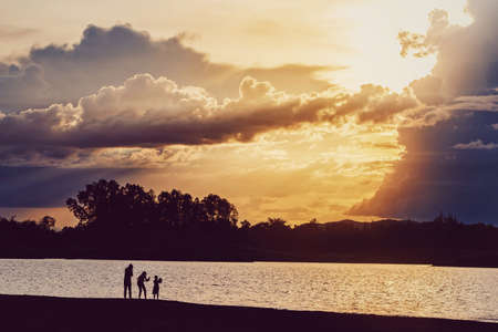 Silhouette people standing at lake with mountain and sunset sky scenic landscape background with copy space. Archivio Fotografico