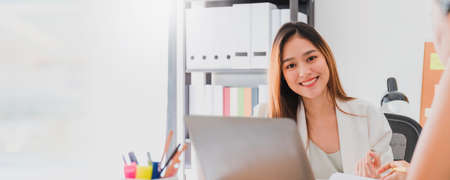Asian beautiful empower woman smiling with friend working at meeting room in office interior background with copy space.Owner businesswoman startup with confident and cheerful.