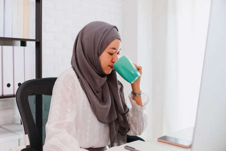 Asian muslim woman student or businesswoman waring hijab.Working from home with computer and drinking coffee.Concept of social distancing working alone at home in the epidemic situation of covid-19.