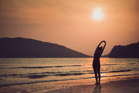 Asian women play yoga on a sand beach by the sea and mountain background in the sunrise morning. Exercise and meditation concept. Archivio Fotografico