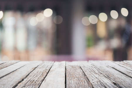 Empty wood table top and blurred coffee shop and restaurant interior background - can used for display or montage your products. Archivio Fotografico