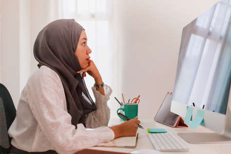 Asian muslim woman student or businesswoman waring hijab.Working from home with computer on table.Concept of social distancing working alone at home in the epidemic situation of covid-19.