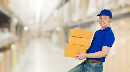 Asian happy delivery man wearing a blue shirt carrying paper parcel boxes isolated on blur interior warehouse in the shopping mall background.Concept of Postal delivery service.