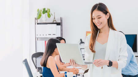 Asian beautiful empower woman smiling and using with laptop at meeting room in office interior background with copy space.Owner businesswoman startup with confident and cheerful.