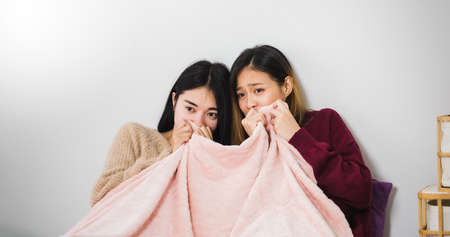 Young beautiful Asian women lesbian couple lover watching horror movie on television on bed  together in bed room at home with fearful face.Concept of LGBT sexuality with happy lifestyle together.