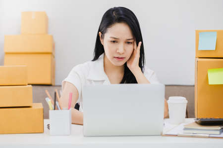 Asian beautiful young businesswoman feeling headache and stress in office space background with product box.Concept of Healthcare and Office syndrome.