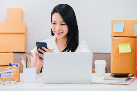 Asian beautiful woman working online business shop at home with smartphone and laptop.Owner businesswoman start up with Accept orders,Check number of products,Prepare to deliver products to customers.