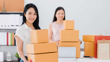 Asian beautiful empower woman working with online business shop at home.Owner businesswoman start up with Accept orders,Check number of products,Prepare to deliver products to customers. Archivio Fotografico