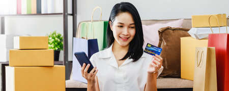 Asian beautiful woman using smartphone with credit card shopping online at home with shopping bag and product box.Convenience in buying online products with modern business technology concept.