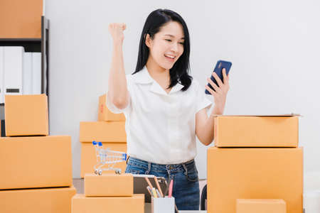 Asian beautiful empower woman working online business shop at home with smartphone.Owner businesswoman start up with Accept orders,Check number of products,Prepare to deliver products to customers. Archivio Fotografico