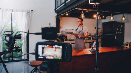 Asian barista man standing in front of the camera and recording vlog video live streaming at bar counter in coffee shop interior background.Sale and promotion online marketing business concept. Archivio Fotografico