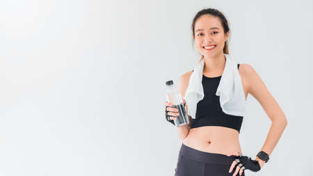 Asian beautiful women holding water bottle after play yoga and exercise on white wall background with copy space.Exercise for Lose weight, increase flexibility and tighten the shape. 스톡 콘텐츠