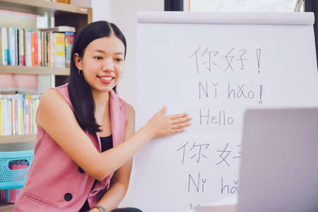 "Asian woman teacher teaching remotely at home office with online technology laptop.Teaching Chinese language for Students at home school.Translation on paper text ""Hello-How are you?"""