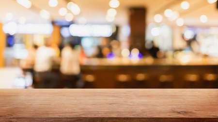 Empty wood table top and blurred coffee shop and restaurant interior background - can used for display or montage your products. Stock Photo