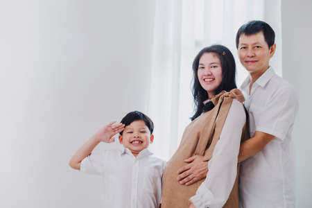 Happy Asian family with Mother is pregnant embraced by father and son at home background.Concept of maintaining health during a happy pregnancy. Foto de archivo