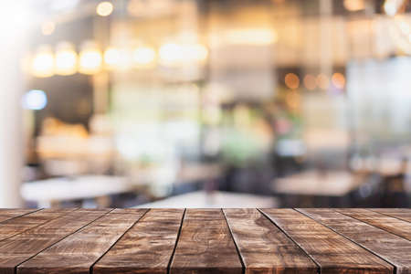 Empty wood table top and blurred coffee shop and restaurant interior background - can used for display or montage your products.