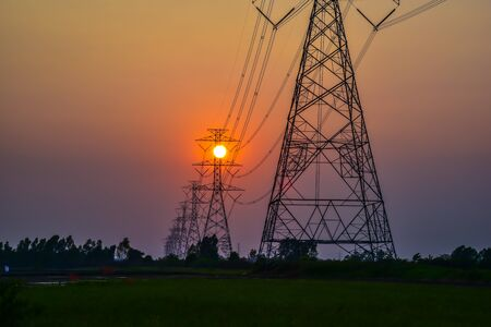 over voltage: Sunset over High voltage pole Stock Photo