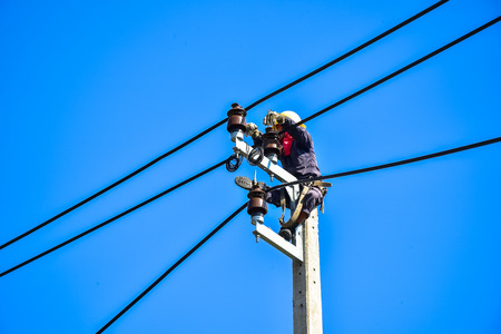 Electrician perform maintenance on the transmission towers with use of claws- manholes and belt Stock Photo
