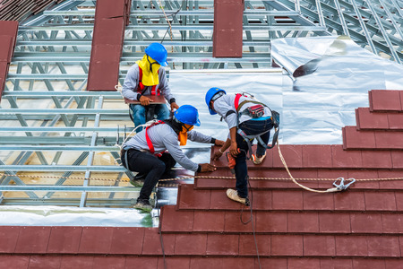Workers are tiling new roof tiles. Фото со стока - 83151963