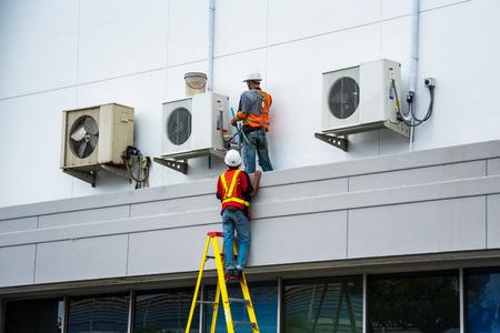 Il tecnico del condizionamento d'aria sta servendo i condizionatori d'aria. Archivio Fotografico - 83535030