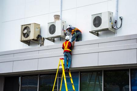 Técnico de ar condicionado estão atendendo condicionadores de ar. Foto de archivo - 83327229