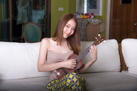 Beautiful asian girl playing ukulele in the living room.