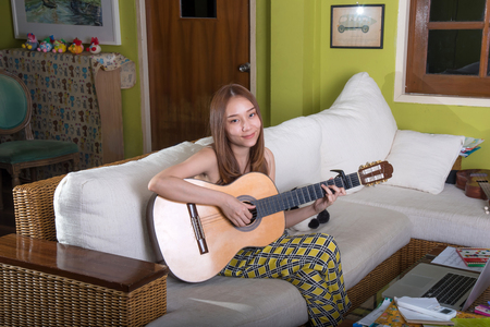 Beautiful asian girl playing guitar in the living room. 版權商用圖片
