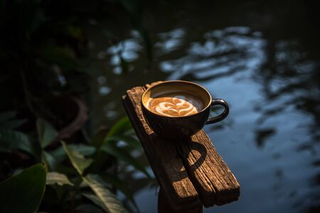 Black ceramic coffee cup on wooden table or counter with morning nature light in garden