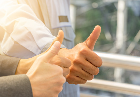 Team giving thumb up as sign of Success Business Teamwork Concept.