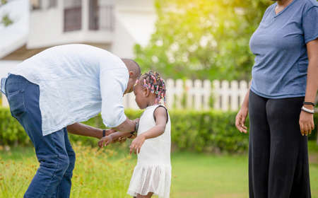 Happy father mother and daughter playing together outdoor, Cheerful african american family enjoying in the park, Happiness family concepts 写真素材