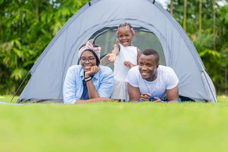 Cheerful african american family enjoying in the park, Mother father and daughter playing camping at outdoor, Happiness family concepts Stockfoto
