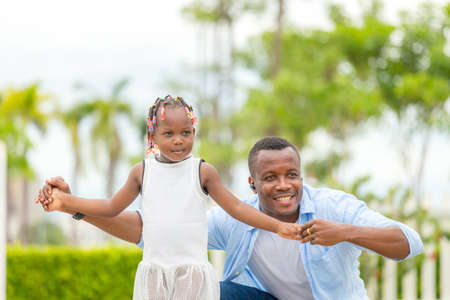 Happy father playing with daughter, Cheerful african american girl playing with her father