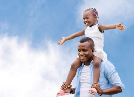 Happy father carrying daughter on shoulders, Cheerful african american girl on the shoulders of his father with clipping path Stockfoto