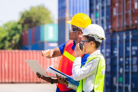 Worker man in hardhat and safety vest holding laptop and Female foreman talks on two-way radio control loading containers box from cargo