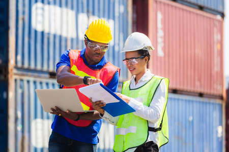 Female foreman safety vest using clipboard checklist and Worker man in hardhat holding laptop for control loading containers box from cargo