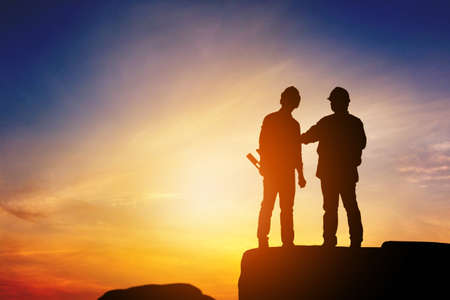 Silhouette of Engineer and worker standing on stone thinking of project sunset in evening time. Stock Photo