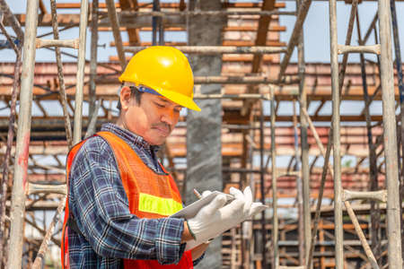 Worker man in hard hat holding clipboard checklist at construction site Banco de Imagens