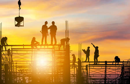 Silhouette of Engineer and worker on building site sunset in evening time. Stock Photo